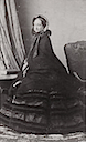 1860 Eugenie in crinoline, paletot, and bonnet looking at photographer