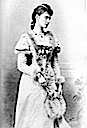 1892 Princess Alexandra standing wearing a fur-trimmed dress and holding a fur-trimmed fan
