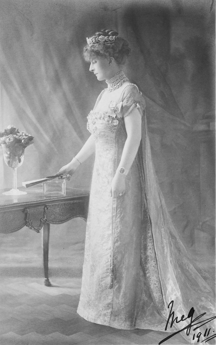 ca. 1911 Margaret Evelyn Cambridge standing in left side profile and holding a fan in her right hand. She wears the Mary Adelaide of Teck diamond crescent tiara From www.pinterest.com/katmaxoz/20th-century-fashion-in-photos